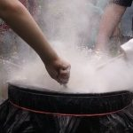 A group of kids experiment with flour and a drum.